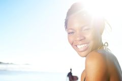 Cheerful young black woman at the beach stock image