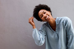 Cheerful young black woman with hand in hair stock photos
