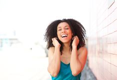 Cheerful young black woman laughing outdoors. Close up portrait of a cheerful young black woman laughing outdoors Stock Images
