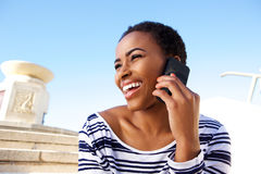 Cheerful young black woman listening to cell phone Royalty Free Stock Photography