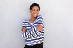 Cheerful young black woman standing against gray wall Royalty Free Stock Image