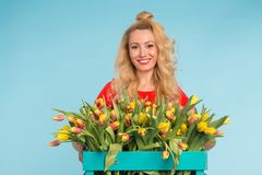 Cheerful young blonde woman florist with box of tulips over blue background royalty free stock image