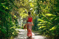 Cheerful young boho style woman walking by the road with tropica Stock Photos