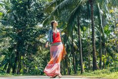 Cheerful young boho style woman walking by the road with tropical background royalty free stock photos