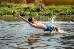 Happy young boy enjoying swimming on river during summer holidays. Happiness and happy childhood concept. Cheerful young boy enjoying swimming on river during stock photos