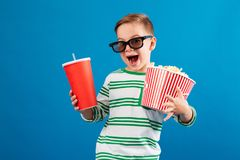 Cheerful young boy in eyeglasses preparing to watch the film Stock Image