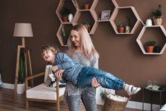 Cheerful little boy having fun with mother on sofa royalty free stock photos