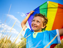 Cheerful Young Boy Playing Kite Outdoors Stock Photo