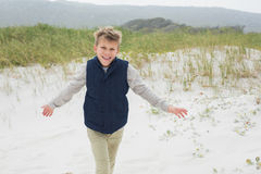 Cheerful young boy running at beach. Portrait of a cheerful young boy running at the beach Royalty Free Stock Photo
