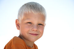 Cheerful young boy smiles. Young blonde boy in orange shirt Royalty Free Stock Image