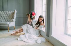 Cheerful, young bride holds a rustic wedding bouquet with peonies on panoramic window background. Close-up portrait. A. Cheerful, young bride holds a rustic royalty free stock photos