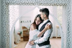 Cheerful young bride smiling and hugging groom while he kisses her in the head and embraces her waist. Beautiful. Newlyweds posing in vintage room. Close-up Royalty Free Stock Photography