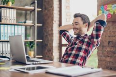 Cheerful young brunet guy is watching at his laptop screen, at h. Is work place, with arms behind the head, resting, smiling, in the office Stock Photos