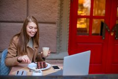 Cheerful girl sitting in a cafe, eating a chocolate dessert and drinking a coffee drink, and smiling. Outside. stock photo