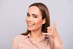 Cheerful young brunette lady with beaming smile is gesturing to. Call her with a hand. She is wearing casual smart beige shirt, on a light grey background Stock Images
