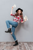 Cheerful young brunette lady holding money. Stock Photos