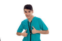 Cheerful young brunette male doctor with stethoscope in uniform looking at the camera and showing thumbs up isolated on Royalty Free Stock Image