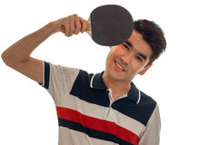 Cheerful young brunette man in uniform practicing table tennis and smiling on camera isolated on white background Stock Photography