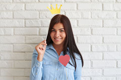 Cheerful young brunette posing while holding a paper crown Stock Images