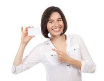 Cheerful young brunette showing a white business card Royalty Free Stock Image