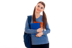 Cheerful young brunette student girl with blue backpackand a lot of books in her hands posing and looking at the camera Royalty Free Stock Images