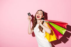 Cheerful young brunette woman holding credit card and shopping bags Stock Photo