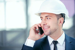 Cheerful young builder is communicating on the Royalty Free Stock Photography