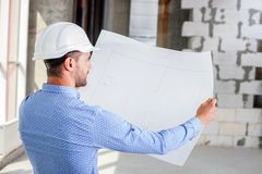 Cheerful young builder is studying the layout of. Handsome architect is analyzing the sketches of building. He is looking at it with aspirations. The man is royalty free stock photography