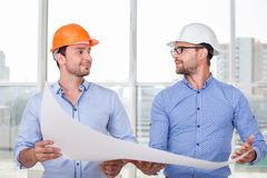 Cheerful young builders are discussing a new Royalty Free Stock Images