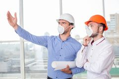 Cheerful young builders are discussing the plan of Stock Image