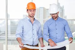 Cheerful young builders are discussing a plan of Royalty Free Stock Photography
