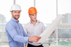 Cheerful young builders are looking at sketches of Royalty Free Stock Photography