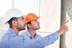 Cheerful young builders are working on a project. Attractive architect is explaining to a foreman the main concepts of construction. He is pointing his finger Royalty Free Stock Image