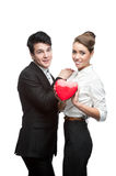 Cheerful young business couple holding red heart Royalty Free Stock Photo