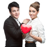 Cheerful young business couple holding red heart Royalty Free Stock Image