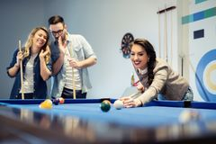 Cheerful business team playing billiard after work Stock Image