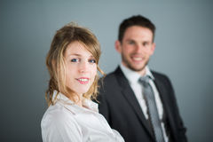 Cheerful young business woman with male coworker behind her Royalty Free Stock Image