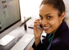 Cheerful young business woman at office using cellphone Royalty Free Stock Photo