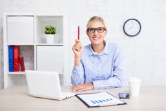 Cheerful young business woman sitting in office and showing idea Stock Photo