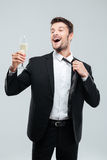 Cheerful young businessman drinking champagne and celebrating Royalty Free Stock Image