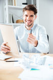 Cheerful young businessman giving notepad and pen to you. In office Stock Photography