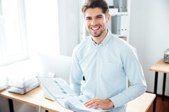 Cheerful young businessman holding folder with documents in office Stock Photos