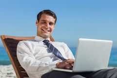 Cheerful young businessman lying on a deck chair with his comput Stock Photography