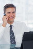 Cheerful young businessman on the phone while working on his tab. Let in bright office Stock Image