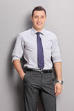 Cheerful young businessman posing on gray background royalty free stock images