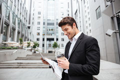 Cheerful young businessman reading newspaper and drinking coffee Stock Photography
