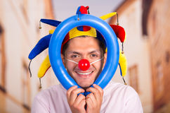 Cheerful young businessman with a red clown nose and colorful harlequin hut in his head playing with a blue ballons Royalty Free Stock Photo