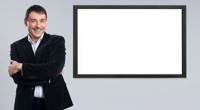 Cheerful young businessman showing blank pc monitor Royalty Free Stock Image