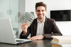 Cheerful young businessman showing money using laptop computer. Photo of cheerful young businessman in home indoors. Looking camera showing money using laptop Stock Photo