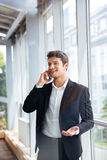 Cheerful young businessman talking on cell phone in office Royalty Free Stock Photos